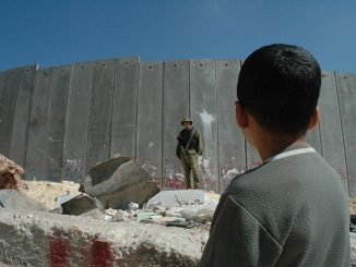 Boy and soldier at Israeli wall